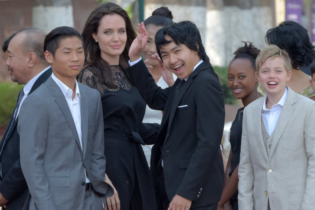 "Nearly five months after Angelina Jolie filed for divorce from Brad Pitt, the actress is back in the spotlight. On Saturday, Angelina pulled double duty and attended a panel and the world premiere of her new film, First They Killed My Father, in Siem Reap, Cambodia, with her six kids — Maddox, 15, Pax, 13, Zahara, 11, Shiloh, 10, and twins Knox and Vivienne, 8 — in tow. Clad in a silky black dress, Angelina appeared to be in good spirits as she waved to nearby onlookers and spoke at a press conference with actress Sareum Srey Moch. Both Maddox and Pax were involved in the film's production, but it was an especially big day for Maddox, who was born in Cambodia (Angelina adopted him in 2002). During the premiere, Angelina spoke about her deep connection to the country, saying, ""Without Cambodia I may never have become a mother. Part of my heart is and will always be in this country. And part of this country is always with me: Maddox.""   Maddox also got up on stage and gave a speech of his own, saying, ""Thank you everyone for attending tonight. We finally made it. It's a great honor to present this film to all of you, and to stand by my mother and my family."" But perhaps the cutest part of the event was when little Shiloh took the microphone and told the audience in Khmer, ""My name is Shiloh and I love Cambodia."" While Angelina has been maintaining a low profile, her divorce from Brad has been at the top of headlines. Just last month, the duo's reps released a joint statement, saying, ""The parents are committed to act as a united front to effectuate recovery and reunification."" As the estranged couple continue to finalize their divorce, it's nice to see Angelina looking so happy."