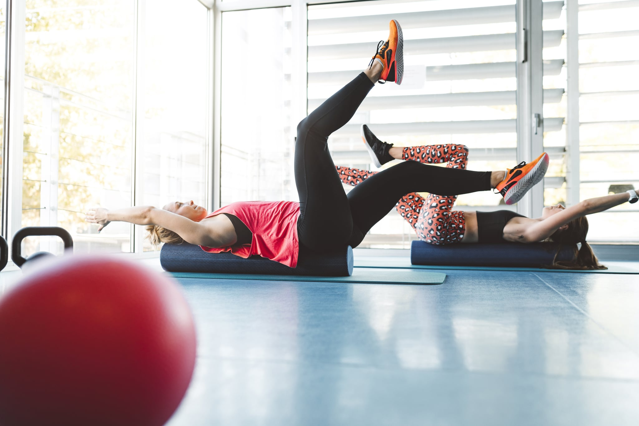 Two young fitness woman athletes doing a dead bug exercise on a foam roller, to work on their core muscles and stability.