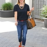 Brighten your blues with red pumps, a statement necklace, and a Louis Vuitton It bag à la Reese.