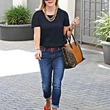 Brighten your blues with red pumps, a statement necklace, and a Louis Vuitton It bag à la Reese.