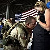 Capt. Tory Burgess of the US Army's 4th Brigade kissed his wife Kathleen's belly on July 16, 2003, at Hunter Army Airfield in Savannah, GA, after returning home from Iraq.