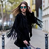 A fringe jacket, bright sunglasses, and a tie choker make for one kickass outfit, as demonstrated by this fashionista in Berlin.
