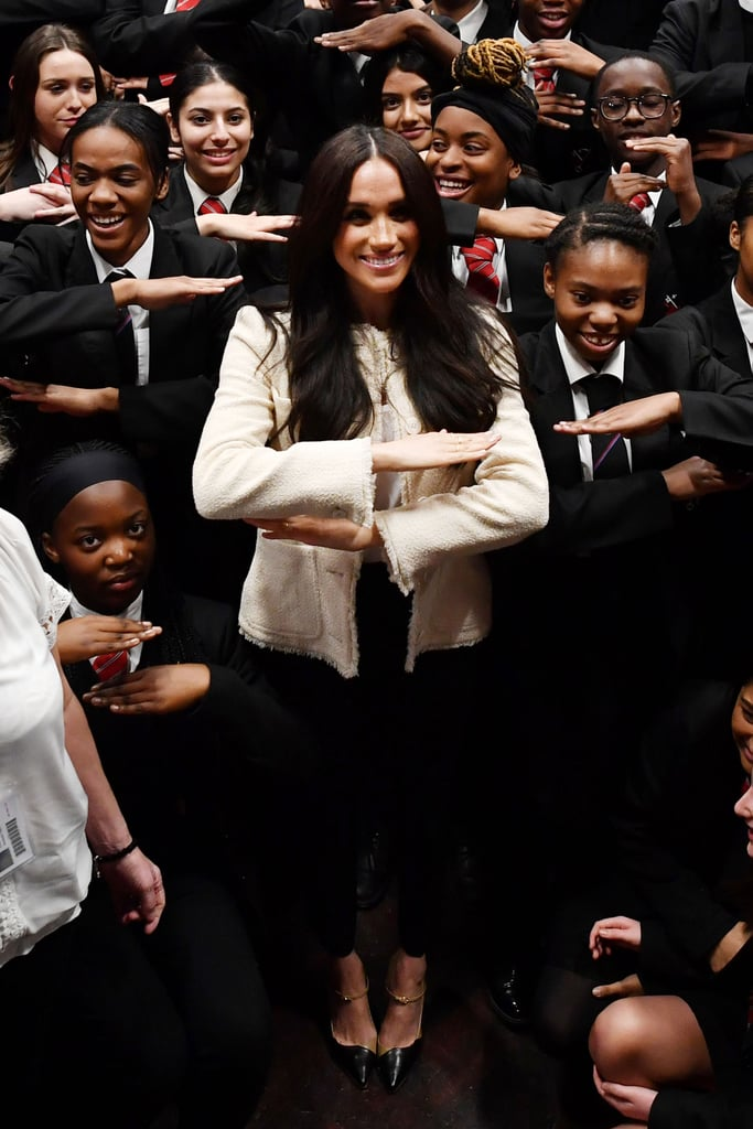 """After celebrating International Women's Day a couple of days early, Meghan Markle is sharing her special honouring with fans. On March 8, the duchess revealed she took a private trip to the Robert Clack School in Dagenham, England, just two days before the global holiday. She posted a gallery of photos and a video montage from the Friday visit that show her speaking with students about the importance of International Women's Day. She also commemorated the 50th anniversary of Britain's Equal Pay Act, which aimed to prevent workplace discrimination against women.  At an assembly, Meghan was joined on stage by Geraldine Dear, one of the workers at Dagenham's Ford motor plant who went on strike for equal pay in 1968, helping to initiate the Equal Pay Act. Speaking to the students, Meghan noted, """"Women who had the strength to really stand up for something that they knew needed to be done is the best example of no matter how small you might feel, how low you may feel on the ladder or the totem pole, no matter what colour you are, no matter what gender you are, you have a voice and you certainly have the right to speak up for what is right."""" She continued, """"I encourage and empower each of you to really stand in your truth, to stand for what is right — to continue to respect each other . . . Let's all rally together to make International Women's Day something that is not just on Sunday, but frankly, feels like every day of the year."""" Meghan has spoken about her dedication to fighting for equal rights before — many times. In 2019, she marked International Women's Day by delivering a poignant speech at a panel discussion about women's issues at King's College in London. At the event last year, she spoke about her history of altruism and activism that begun long before she was a royal.  The International Women's Day appearance comes in a busy week for Meghan, as she and Prince Harry make their last few appearances as senior members of the royal family. Recently, they made stun"""