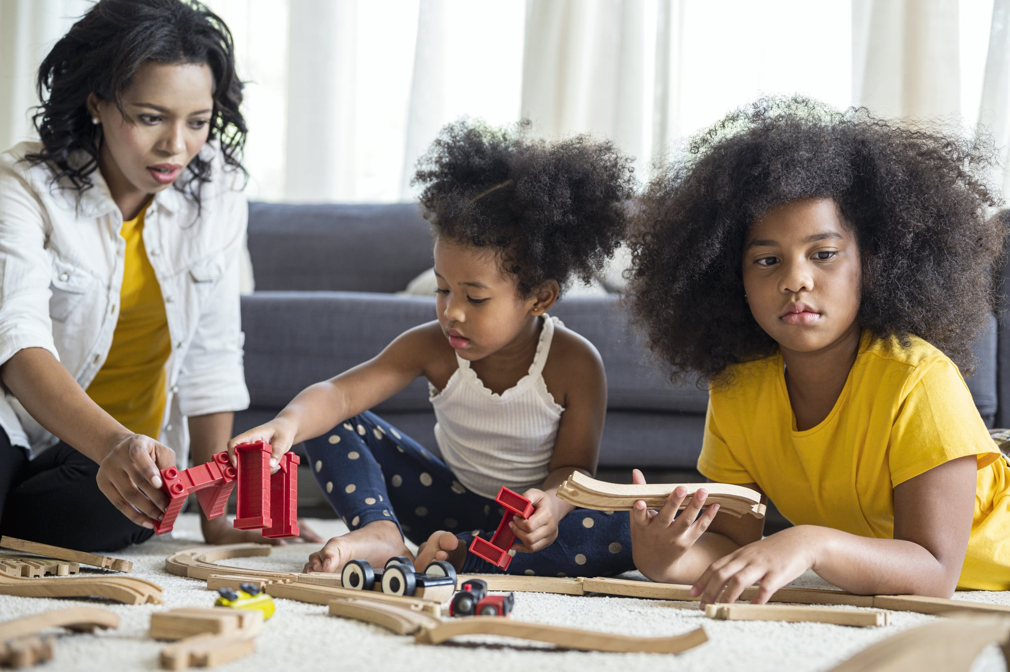 Cute girls entertaining with toy car near her sister on floor. Happy family spending time together in living room on weekend.