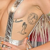 """Miley's first tattoo ever was the phrase """"just breathe"""" on her rib cage in December 2009, which was reportedly done as a tribute to her close friend, Vanessa, who died of cystic fibrosis, and both of her grandfathers, who died of lung cancer. """"It reminds me not to take things for granted. I mean, breathing — that was something none of them could do, the most basic thing,"""" she told Harper's Bazaar. """"And I put it near my heart, because that is where they will always be."""" The """"just breathe"""" tattoo is joined by a moving image dedicated to her late dog, Floyd, who passed away in April 2014, and a naked woman standing in a body of water."""