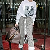 Wearing an oversize Chaos sweatshirt with Stuart Weitzman booties and a Fendi duffel bag.