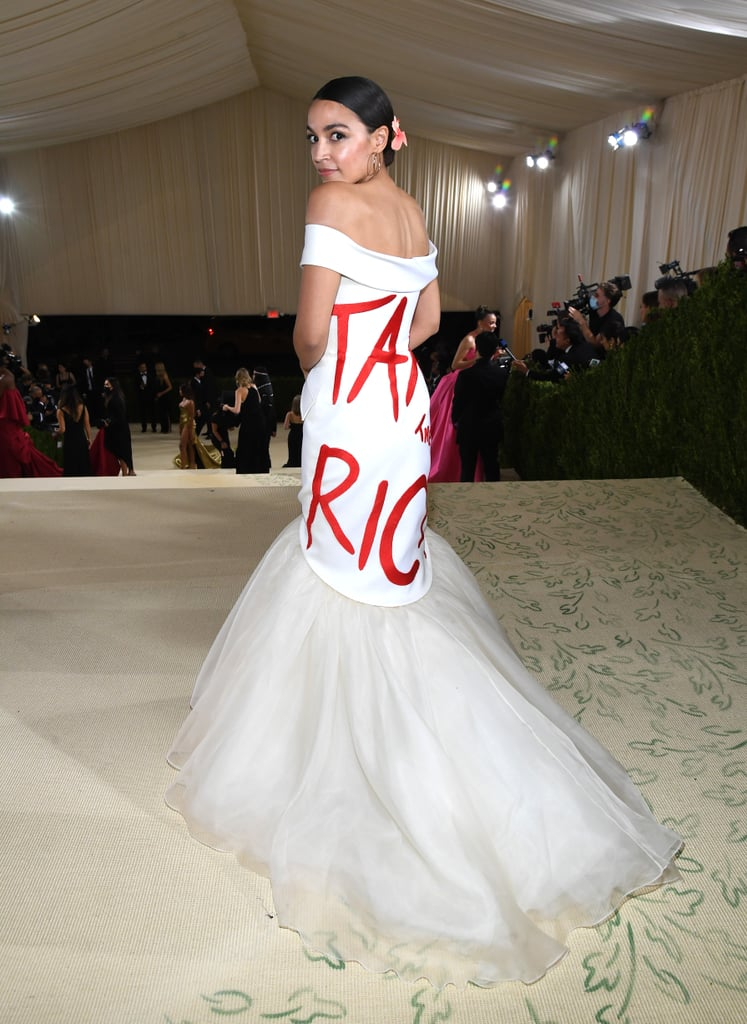 """Alexandria Ocasio-Cortez made quite the debut at Monday night's Met Gala! On first glance, the congresswoman appeared to be wearing a gorgeous off-the-shoulder white gown with a tulle train, but the second she turned around, we saw her iconic political statement: """"Tax the Rich"""" was plastered across the back of the dress in bright red lettering. It's not lost on us that AOC chose the statement Brother Vellies look for one of fashion's most extravagant, glamorous nights. As the brand's designer Aurora James so perfectly said, """"If you're going to come somewhere like the Met Gala and you're a congresswoman, you expect nothing less."""" Alexandria completed the outfit with red heels with flowers, as well as a matching """"tax the rich"""" bag. Ahead, see the look from the front and back."""