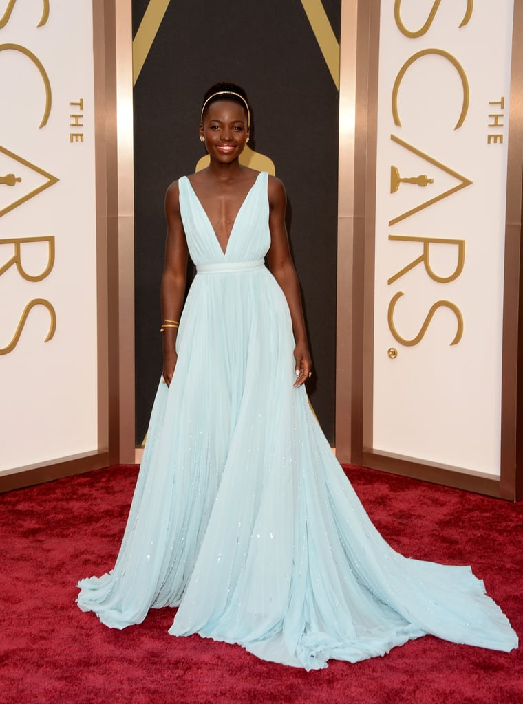 Lupita Nyong'o made her highly anticipated entrance at the Oscars in LA today! The 12 Years a Slave star looked stunning in a blue Prada gown and accessorised it with a winning grin for her Academy Awards debut. Lupita's road to the Oscars red carpet has been paved with accolades and awards; she's garnered heaps of praise for her role as Patsey in the film adaptation of Solomon Northup's memoir and has already picked up trophies for the best supporting actress honour at the Critics' Choice Awards, SAGs, NAACP Image Awards, and Saturday's Independent Spirit Awards. Today, she'll go up against Jennifer Lawrence and Julia Roberts for the Oscar. Keep reading for more on Lupita's first time at the Oscars, and be sure to vote on her look in our fashion and beauty polls! Source: Getty