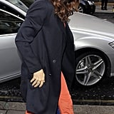 Jessica Biel wore bright salmon pants and a black trench in London.