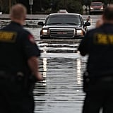 Two officials watch as a truck drives through the flood.