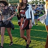 Alessandra Ambrosio wearing a graphic tunic, leather jacket by The Mighty Company, Oliver Peoples sunglasses, and Giuseppe Zanotti boots at the festival.
