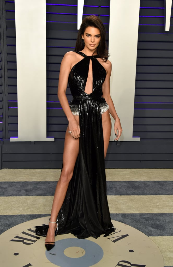 "There definitely seems to be a dress code for the Kardashian-Jenner family when it comes to 2019 award ceremonies, and that dress code is ""we're gonna need more tape."" After Kim Kardashian made waves in a very revealing vintage Thierry Mugler gown when she accompanied her hair stylist Chris Appleton to the Hollywood Beauty Awards, Kendall Jenner decided to take the sexy look to a whole new level at the Vanity Fair Oscars party. Kendall's beaded black and silver dress by Rami Kadi wasn't just backless and slashed to the navel, it was also cut so high on the sides that it resembled two sashes, rather than a skirt. By the looks of it, the dress was designed with a built-in bodysuit to keep everything in place as she moved. Of course, Kendall's no stranger to a revealing look, and she's clearly been practicing her poses at home, as she knew exactly how to work the cameras in the gown. Keep reading for a closer look from all angles — you know you want to!"