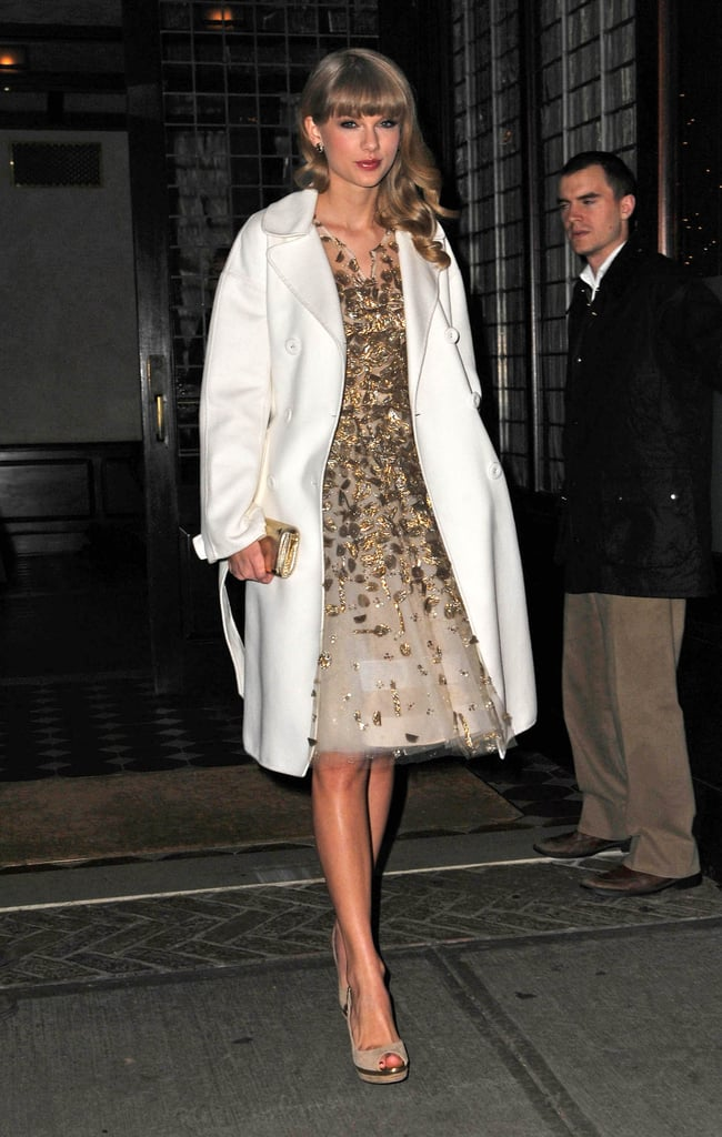 Taylor Swift played up the wow factor of her gilded dress with a simple ivory coat.