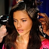 Adriana Lima sat patiently in her hair and makeup chair.