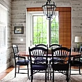 This chic dining room design forwent traditional wallpaper for gray-hued wood planks that contrast beautifully with the warm tone of the hardwood floors.