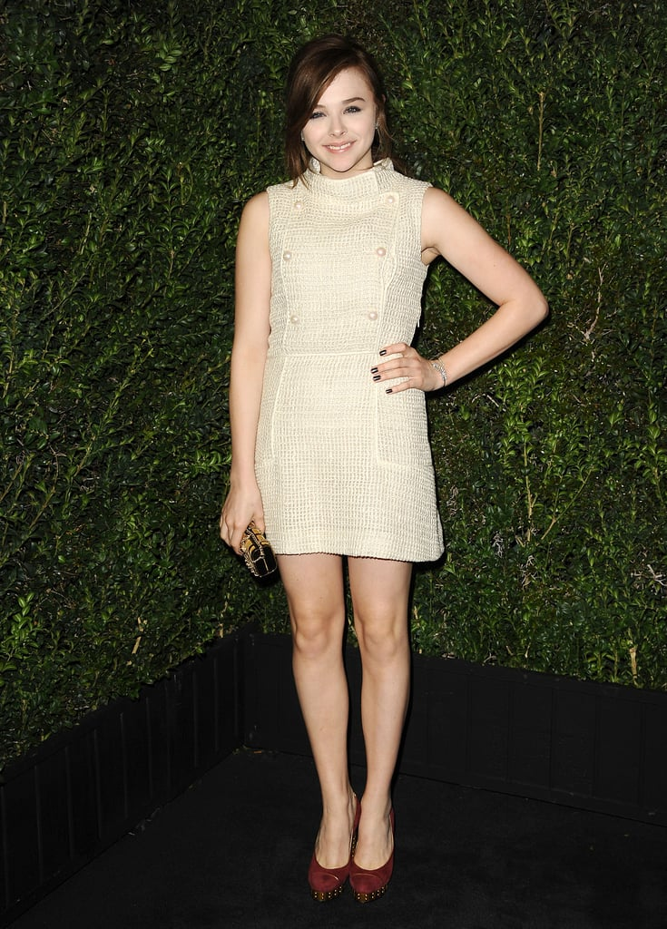 Chloë Moretz showed off her stems in a high-necked Chanel cream-colored tweed dress, which also featured pearl buttons down the front, at the brand's pre-Oscars dinner.