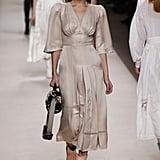 Walking in Fendi wearing a silk dress.