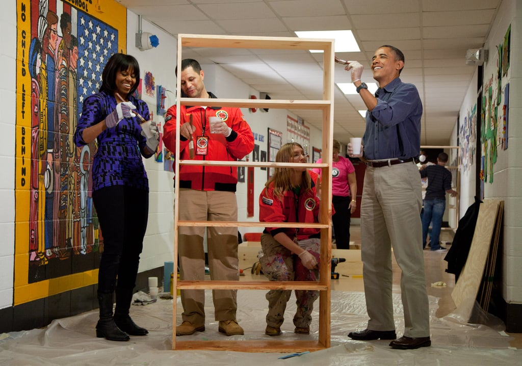The first couple participated in a National Day of Service event, staining a bookshelf at Burrville Elementary School in DC.