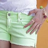 Kate sporting lime green AG Jeans shorts with a white tee and a JewelMint charm bracelet.