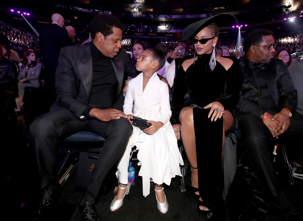 Blue Ivy Carter was wedged between her famous parents, JAY-Z and Beyoncé Knowles, at the Grammys in NYC on Sunday night. The adorable 6-year-old sat front row in an all-white outfit at the event, marking the third time she's attended with her mom and dad; if you recall, Blue mingled with Rihanna back in 2015 and basically stole the entire show during James Corden's Carpool Karaoke bit in 2017. Beyoncé and JAY-Z have been out and about for the better part of Grammys weekend; they hosted the annual Roc Nation brunch on Saturday afternoon, then did a costume change for Clive Davis's annual pre-Grammys party, where JAY was honored with the Grammys Salute. They also had this woman completely shook with their presence, naturally. Keep reading to see the Carter family's night at the Grammys!