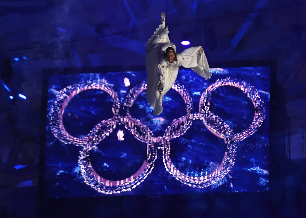An angelic woman was suspended beside the Olympic rings.