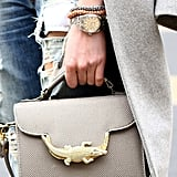 A gold alligator crawled across this chic gray satchel.