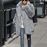Olivia's skinny jeans and sneakers got a luxurious upgrade thanks to her chic Winter coat.
