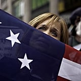 A flag-bearing woman listens to the 9/11 Freedom Rally speeches in NYC on the 10th anniversary of the Sept. 11 terrorist attacks.