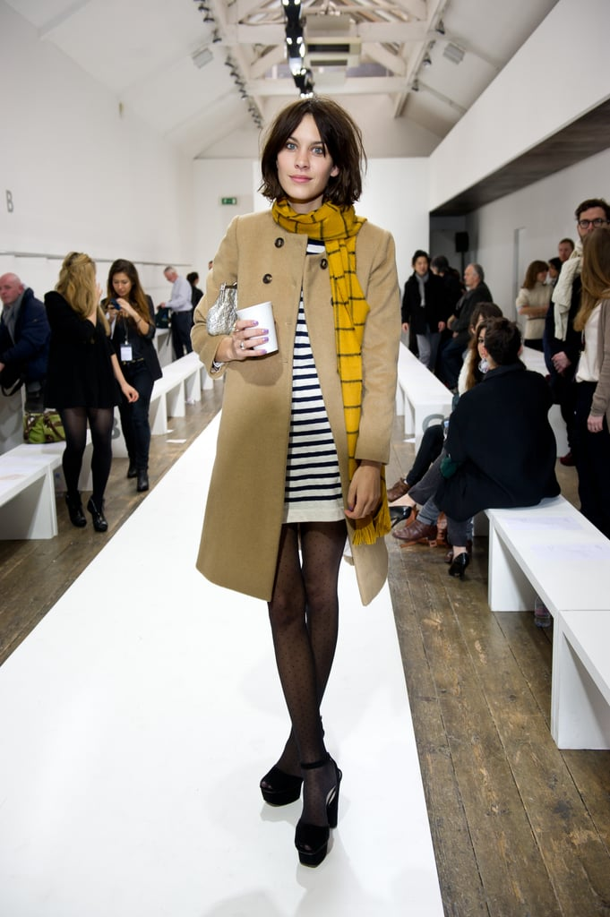 Front row at A/W London Fashion Week in a Breton striped sweater dress and tights teamed with a plaid scarf and trench.