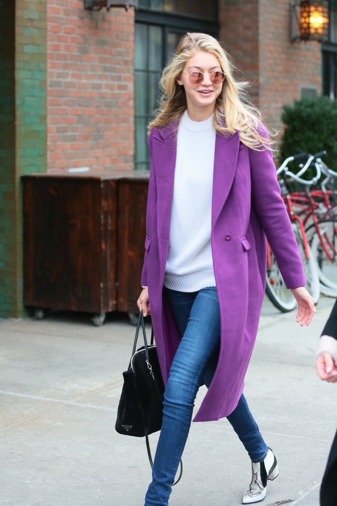 Wearing skinny jeans with a white sweater, purple coat, and patterned white booties.