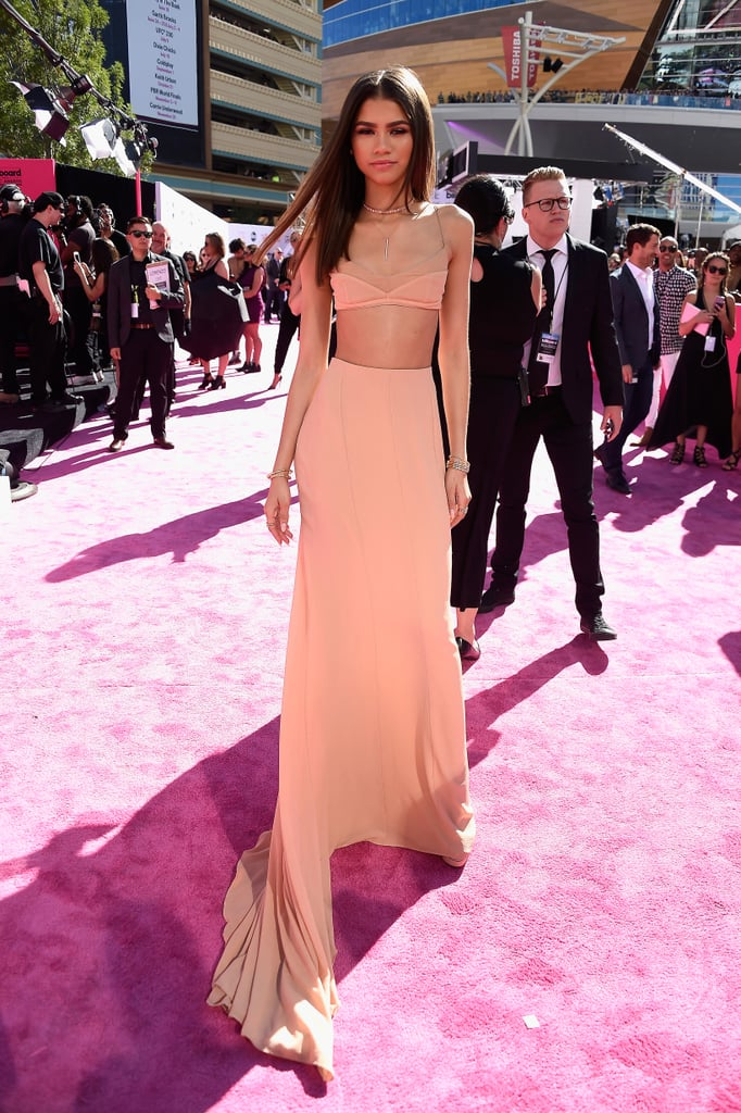 Leave it to Zendaya to show up to the Billboard Music Awards looking like an angel sent from heaven. On Sunday, the singer made her way to Las Vegas, where she drew eyes in a sexy crop top and matching skirt. Not only did she look gorgeous while strutting her stuff on the pink carpet, but she was all about the fans as she stopped to pose for photos with them. Inside, Zendaya linked up with pals Keke Palmer and Troye Sivan, and took the stage alongside Wiz Khalifa to present The Weeknd with the award for best R&B song. Take a look at even more of the night's stunning arrivals.