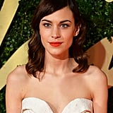 Alexa Chung was looking quite festive in her Winter white dress, which she wore with glossy curls, bold brows, and a cerise lip.