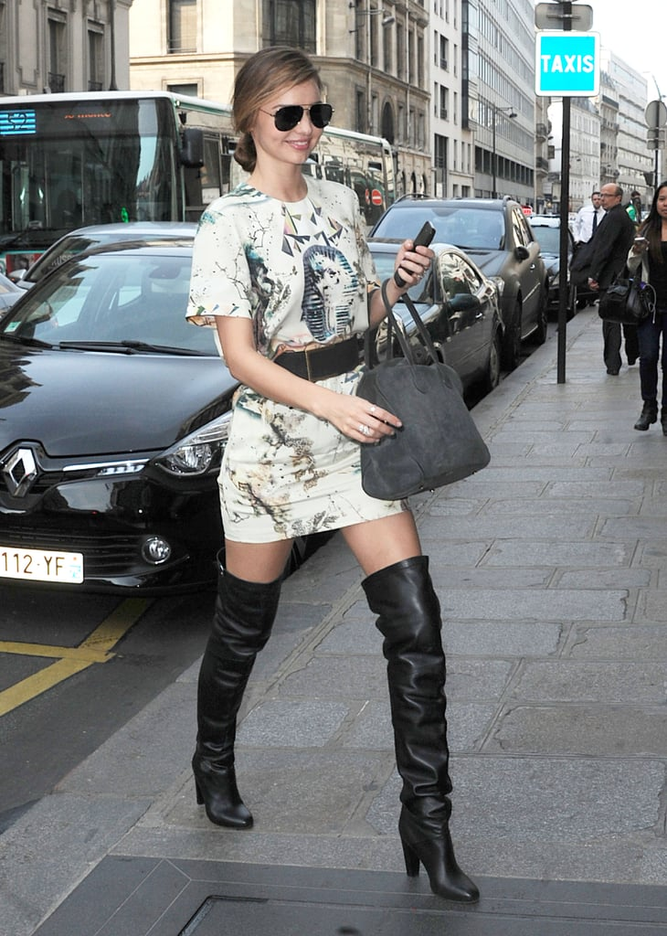 While in Paris, Miranda Kerr let her long legs take focus by putting them in a pair of black leather over-the-knee boots. She finished with an equally sassy printed minidress and aviator sunglasses.