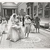 The wedding party walked through the halls of Buckingham Palace.