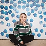 Social Media influencer Alexa Losey sat for a photo in front of the wall.