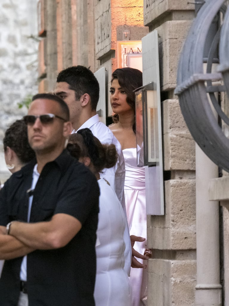 """For the """"white out"""" party at the Hotel de la Mirande, Priyanka was spotted in a strapless satin gown that featured a thigh-high slit."""