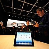 Members of the press discuss the new iPad.