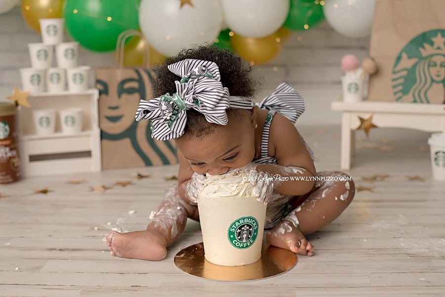 """Lynn Puzzo's obsession with Starbucks coffee runs deep. So deep, in fact, that the Fayetteville, GA, photographer used the iconic brand to make a big splash by staging an adorable cake smash photo shoot featuring a 1-year-old girl named Aria.  """"The idea for this session came from my obsession with Starbucks!"""" she told POPSUGAR. """"I found the outfit and ordered a cake, and then found the model and put the set together to bring my vision to life. I was super excited about it and didn't tell a soul — including the model! — I wanted it to be a total surprise! I searched the internet and wasn't able to find any other Starbucks-themed cake smash sessions!""""  Clearly, her idea panned out! Scroll through to get a look at the adorable, Frappuccino-themed photos.       Related:                                                                                                           There's Just Something About These Photos of Babies Smashing Cakes That Will Fill Your Insides With Joy"""