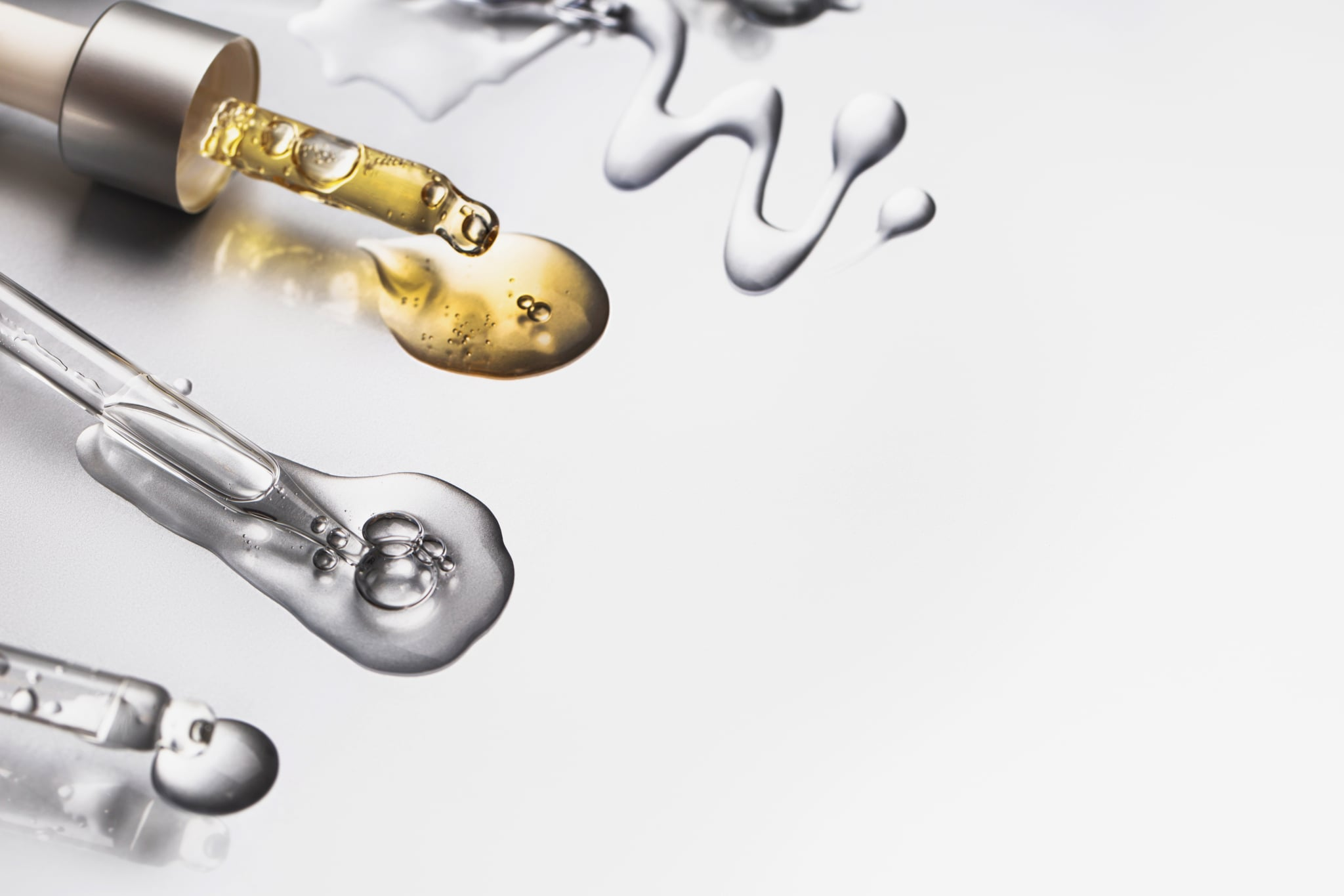 Group of pipettes with serum and oil on luxury silver background