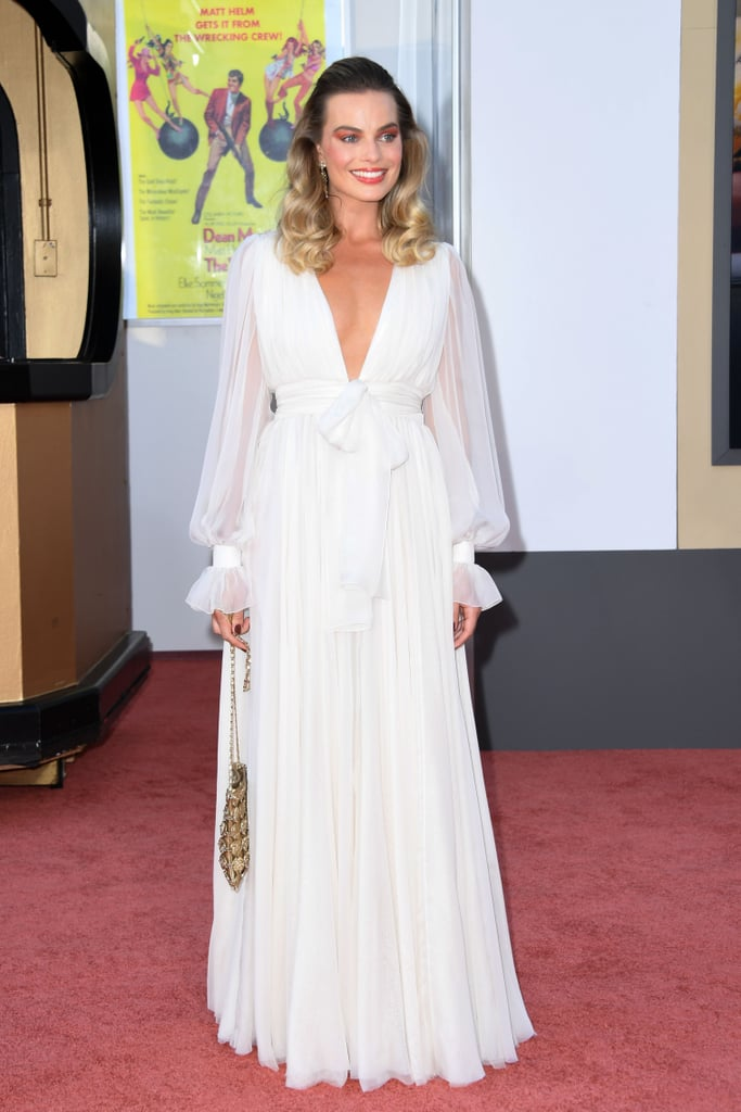 Margot Robbie practically floated onto the Once Upon a Time in Hollywood red carpet on Monday night wearing an angelic gown that we'll be thinking about for days. Surrounded by some of the industry's brightest stars, the 29-year-old actress radiated classic glamour in a Chanel outfit at the movie's LA premiere. The gown featured a plunging neckline, billowing bishop-style sleeves, and a large bow detail around her waist. She completed the ethereal ensemble with dangling earrings and a gold chainmail purse. It's no surprise Margot chose Chanel for her red carpet look, given that she's the longtime face of the brand. This particular outfit, however, was also meticulously chosen to match a 1970s Vogue spread made famous by model Lauren Hutton. The era aligns well with Quentin Tarantino's film, and the life and death of Margot's character, Sharon Tate, who died in 1969. Ahead, see more photos from Margot's night on the red carpet. This is a dress we'll be dreaming about.