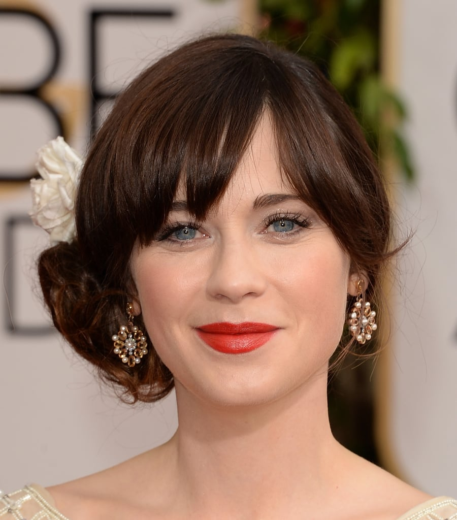 With a statement red lip and flower-adorned chignon, Zooey Deschanel stuck to her signature style for tonight's big show.