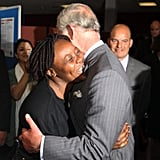 Prince Charles is embraced while meeting with local residents at the Tottenham Green Leisure Centre.