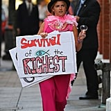 "A young woman protested with a sign saying ""survival of the richest."""