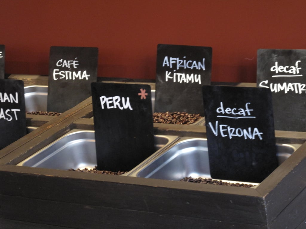 Single-origin, whole-bean coffees are displayed in bulk bins at the counter.