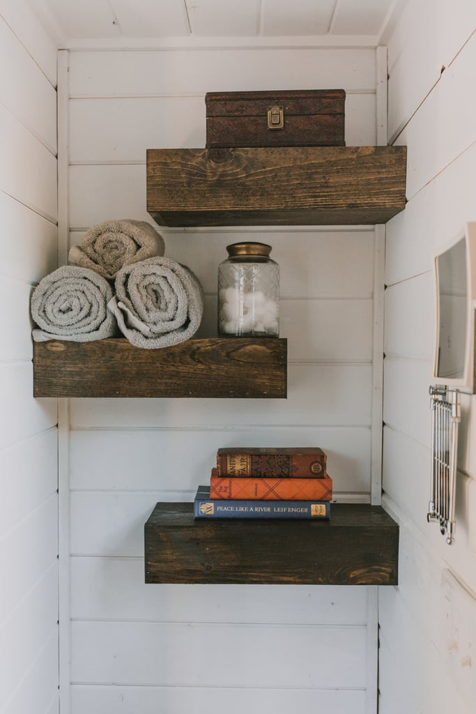 The bathroom's staggered floating shelves not only look good, but can also accommodate items at varying heights. Another trick? Using an adjustable mirror instead of a large vanity mirror.