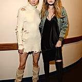 . . . Thank goodness they figured it out. Gigi supported Kanye alongside her best friend Kendall in a silky Nili Lotan slip dress, Nicholas Kirkwood thigh-high boots, a black choker, and slick olive Ben Taverniti bomber jacket.