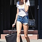 Nicole Trunfio stuck to the cool girl's Summer uniform: denim cutoffs and a white tee. A black hat, studded loafers, and oversize sunglasses jazzed things up even more.