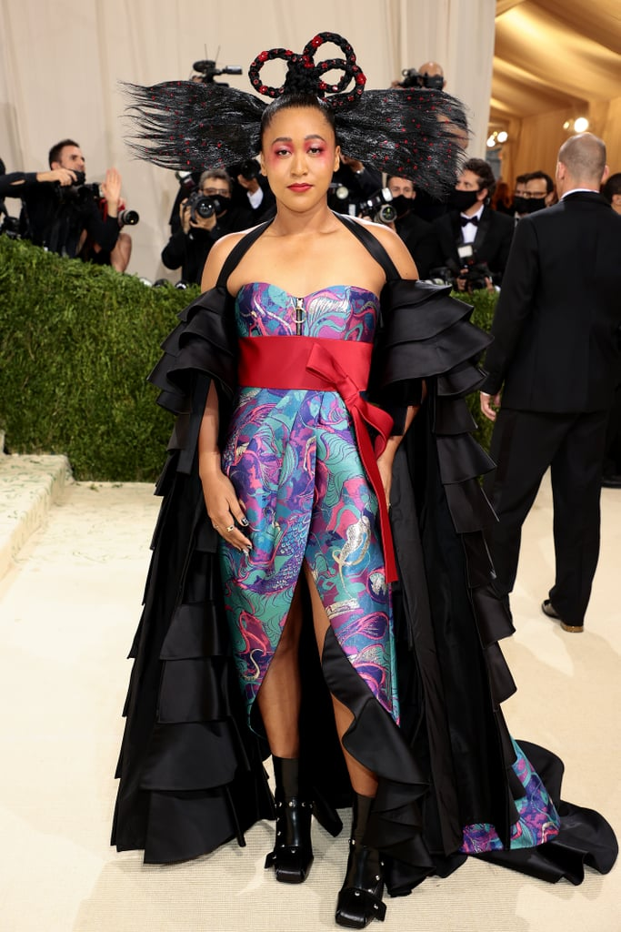 """Naomi Osaka is here to make a statement. On Monday night, the four-time Grand Slam champion swapped her tennis gear for designer fashion at the 2021 Met Gala. Naomi is one of the cochairs of the annual fashion event, and as a Louis Vuitton ambassador, it only made sense that she would team up with the brand for a very special Met Gala dress. Naomi wore a dress designed by Nicolas Ghesquière and her older sister, Mari Osaka. """"Americana to me means a mix of all cultures, and this look incorporates both of my heritages: Haitian and Japanese,"""" she said during her red carpet interview.  The silk corset dress featured a beautiful red bow and a black layered cape with 22 ruffles, to be exact! According to Vogue, the design of the dress began as a """"digital watercolor art piece"""" by Mari, which was adorned with koi fish as a tribute to their Japanese heritage. """"The fact that Nicolas, Mari, and I could come together bringing this to life is something I am very honored to be a part of,"""" Naomi said.  Check out photos of Naomi's stunning and incredibly meaningful Louis Vuitton dress at the Met Gala ahead, which she attended with boyfriend Cordae.      Related:                                                                                                           Every Look From the 2021 Met Gala Red Carpet That We Can't Stop Talking About"""
