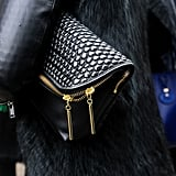 The textural detailing and gold zippers on this oversize black clutch are to die for.