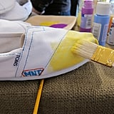 "Associate editor Marisa Tom also started with a yellow base and added her initials with colorful Sharpie markers on the side of each shoe. Our Tips For Decorating:   Keep a mason jar filled with water at the ready. We found that diluting our paint colors just a little helped the application process. By watering down the vibrancy, you can manipulate the color scheme to your liking. This is particularly useful if you're going for a tie-dye or ombre effect.  Thicker brushes are way easier to work with — trust us.  There's really no such thing as messing up here. Improvisation (and embracing it) made this project super fun and inspired a bright, unexpected outcome, which we loved.  Make sure to keep the ""stuffing"" of the shoe in place while you paint and as the shoe dries. This way, your shoe will keep its signature TOMS shape."